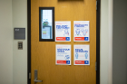 Health and safety posters remind the community of behavioral expectations inside campus buildings. Photo: Douglas Levere