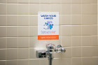 Reminders to wash hands properly are present inside bathroom stalls and above urinals. Photo: Douglas Levere
