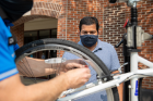 Gaurav Vishwakarma, a PhD candidate in chemical and biological engineering, watches as Scott Bixby tunes up his bike.