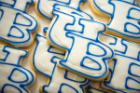"A tradition. Each cookie is hand-cut with a special ""UB logo"" cutter and individually iced and hand-piped with white and ""UB Blue"" frosting."