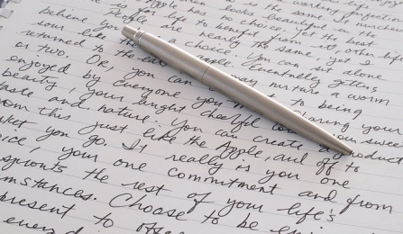 """ Image of a notebook with writing on it and a pen on top""."