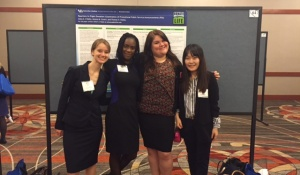 A group of graduate students stands in front of conference poster.