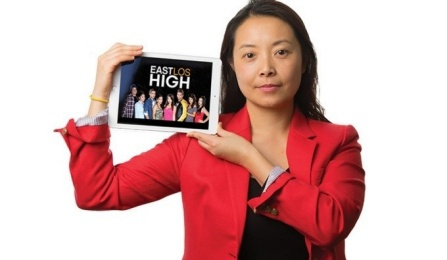 "Helen Wang stands in front of screen holding an image up of the show ""East Los High"" with a white background behind her."