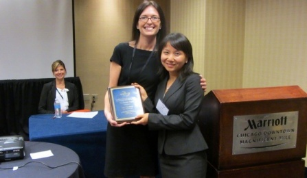 Janet Yang is standing next to a tall woman in a black dress, as they hold up an award. Both woman are smiling. There is another woman sitting in the background smiling at the camera from a distance.