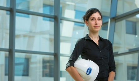 University at Buffalo assistant professor Pinar Okumus stands near window holding a white hard hat