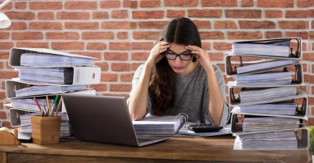 Exhausted businesswoman working at office with stacks of binders on her desk.