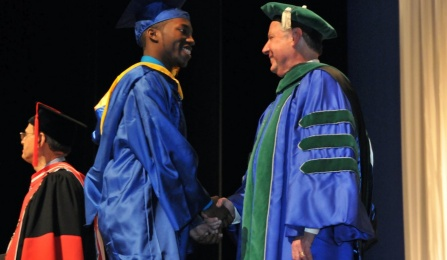 Richard Hunte, BS, biomedical sciences, receives congratulations from Dean Michael E. Cain, MD.