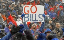"A photo of a Buffalo Bills fan holding a sign that reads, ""Go Bills.""."