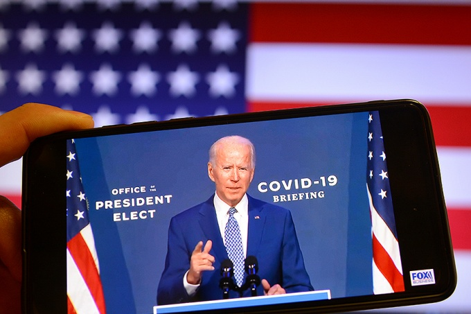 U.S. President-elect Joe Biden speaks during a media briefing in Wilmington on a YouTube video displayed on a screen of a smartphone.
