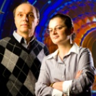 UB physicists Avto Kharchilava and Ia Iashvili standing in front of a colorful background.