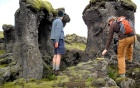 Two men climbing around lava pillars that are around the same height as they are