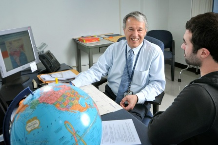 John Sellick talks with a student about global travel.