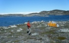 William Philipps standing on rocky ground in Greenland with a tent and the ocean behind him.