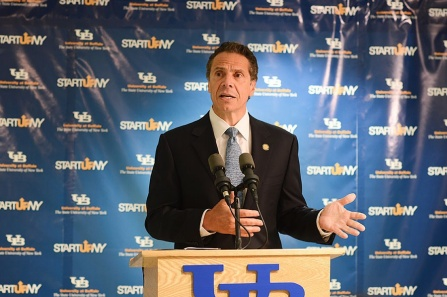 Gov. Andrew M. Cuomo speaking at a podium at UB to announce that eight additional companies will relocate on or near the UB campuses through their participation in Start-Up NY.