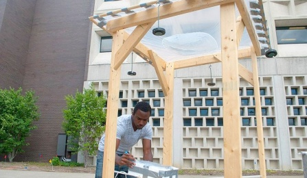 UB student Deshawn Henry and a giant water lens made from plastic sheeting stretched across the top of a wood frame.