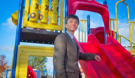 Youfa Wang standing next to a red plastic slide in a children's playground/