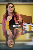Paige Sarlin, sitting at a conference table that reflects her image.