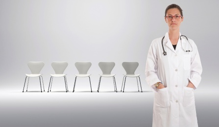 A femail doctor stands in front of an empty row of chairs with a frown on her face.