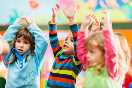 Three preschool children playing, with their arms raised up over their heads