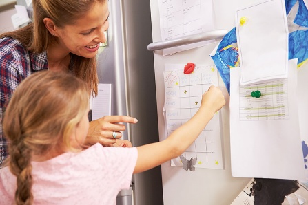 A mom and a little girl look at her reward chart on the refrigerator.