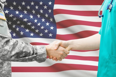A service member and a health care practitioner shake hands in front of the American flag.