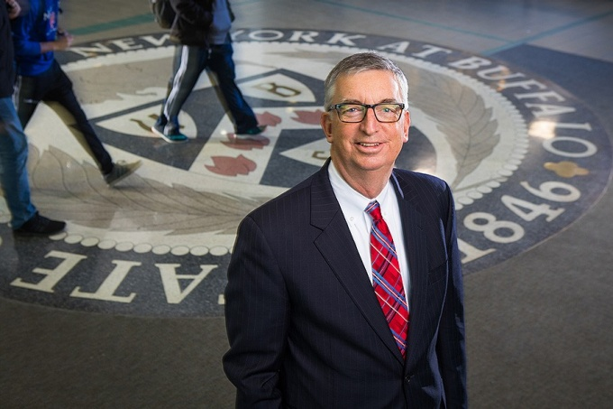 A. Scott Weber standing in the Student Union in front of an official university seal on the floor. He is wearing a white shirt, a red plaid tie and navy-colored suit, and wears glasses.