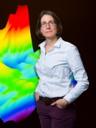 Andrea Markelz in front of a colorful illustration of scientific data.