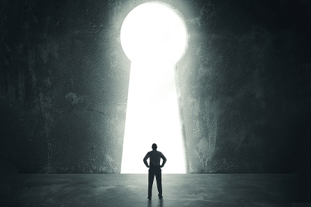 A man stands in front of a giant keyhole.