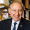 Robert Gallo sitting in a lab while wearing a suit.