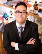 Brian Tsuji standing in lab wearing a black suit.