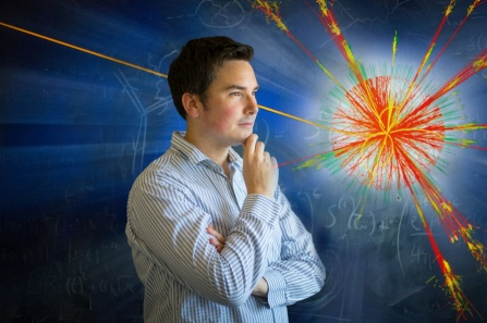 Ciaran Williams stands in front of blackboard with image of particle exploding.