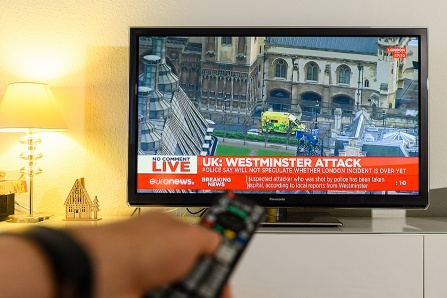 Man holding a remote control watching BBC channel reporting live scenes from Westminster Bridge after armed attack in London.