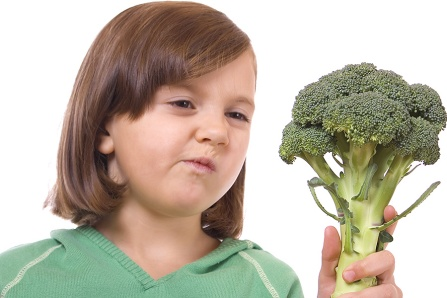 Young girl looking skeptically at a head of broccoli.