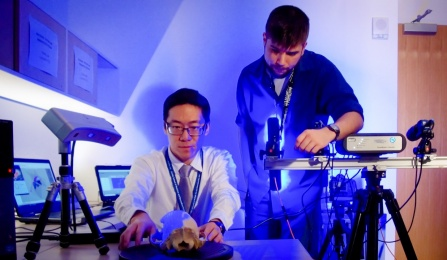 Jack Tseng and master's student Connor Grabowski study a skull in blue light