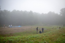 Researchers working in a large clearing on a foggy day.
