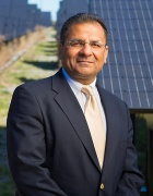 Amit Goyal stands in front of solar power field