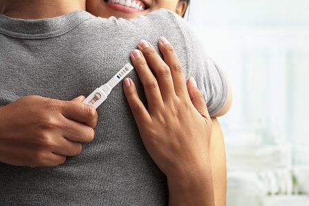A woman holding a positive pregnancy test hugs her male partner.