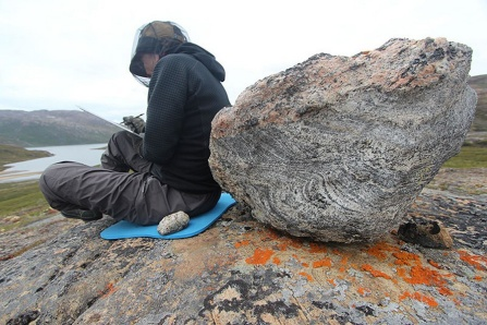Artist Anna McKee sitting next to a boulder in Greenland.