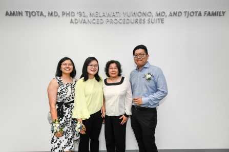"Tjota family posing in front of a wall with the words, ""Amin Tjota, MD, PhD '91, Melawati Yuwono, MD and Tjota Family Advanced Procedures Suite.""."