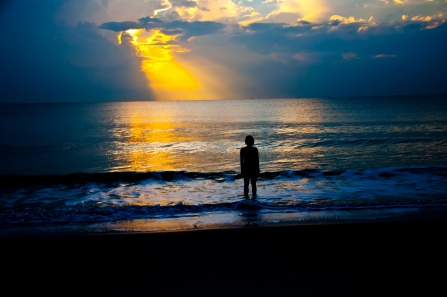 An individual stands on a beach as the sun sets over the ocean.