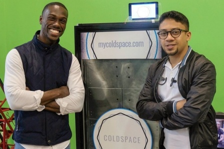 UB alumni Elijah Tyson and Abid Alam standing with a prototype of a specially designed refrigerator.