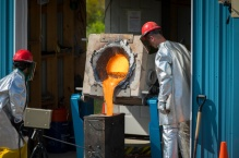 Two scientists in silver protective suits pour lava from a furnace into a rectangular metal container.