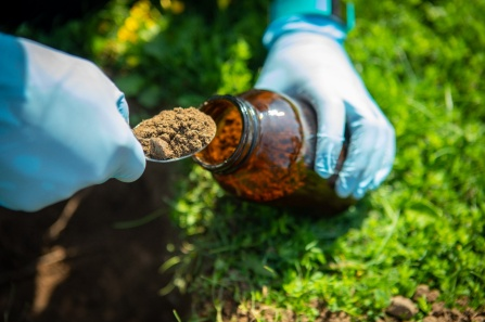 Gloved hands scooping soil into a glass jar.