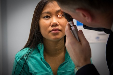 John Leddy does eye exam on adolescent female patient.
