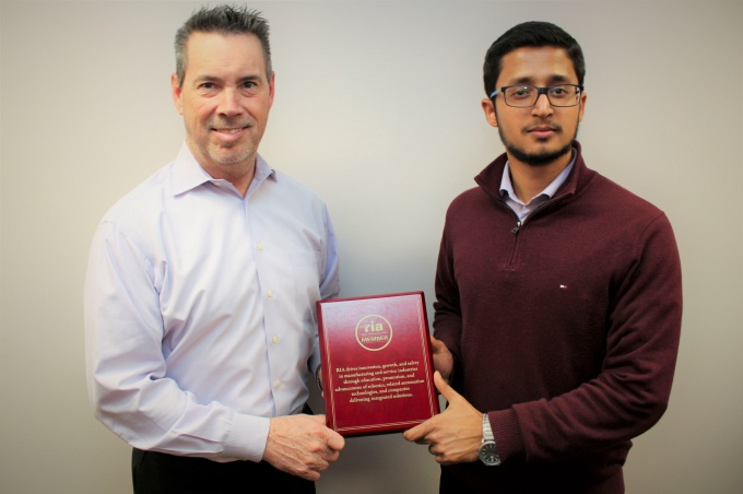 From left: TCIE's Executive Director Timothy Leyh and Project Engineer Akshay Sivadas pose with the RIA member plaque.
