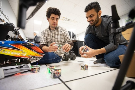 Two UB students work with small drones inside a UB lab.
