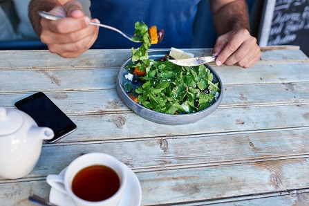 Young man sitting alone at a bistro table having a tea and eating a delicious plate of mixed salad with a knife and fork.