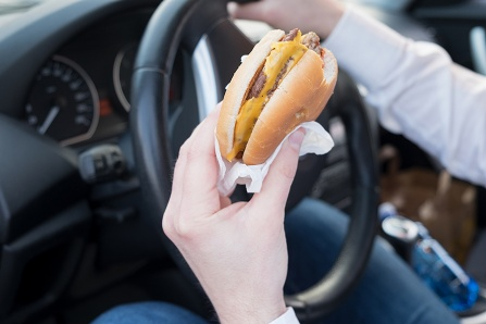 Person eating a fast food cheeseburger while driving.