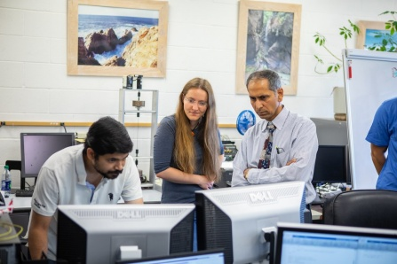 Tarunraj Singh, far right, and two students stand together looking a computer screen.