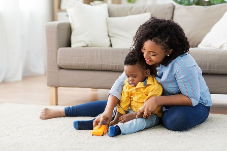 A mother and toddler playing together on the floor.